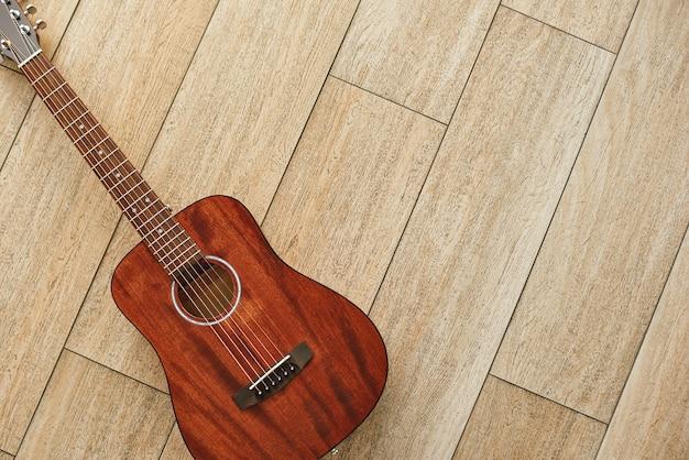 Belleza del instrumento musical. vista superior de la guitarra acústica marrón tirada en el piso de madera. fondo de música. concepto de música. instrumentos musicales