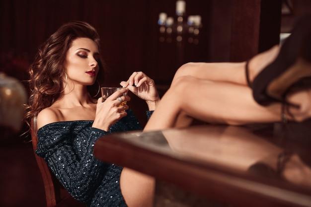 Belleza joven morena sentada en el bar