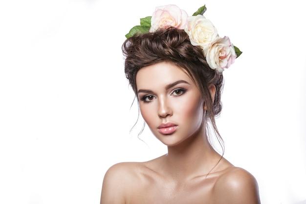 Belleza joven, piel limpia, hermoso maquillaje, trenzas de peinado y flores color de rosa en el cabello. tonalidad clara sobre fondo blanco.