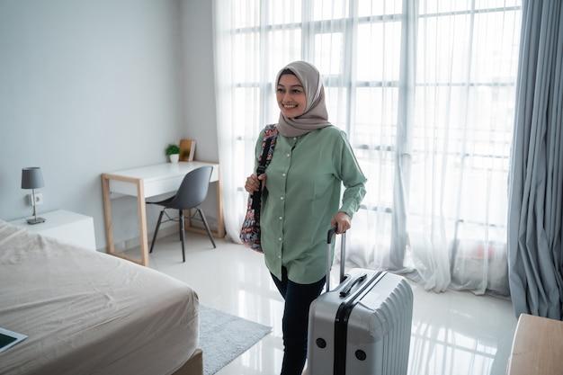 Belleza joven viajero hijab caminar y llevar su bolso y sosteniendo la maleta