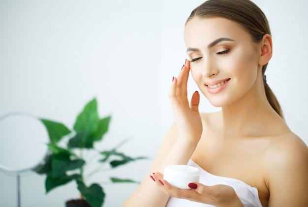 Belleza juventud cuidado de la piel concepto - cerrar hermosa mujer caucásica rostro retrato aplicar un poco de crema en la cara para el cuidado de la piel.