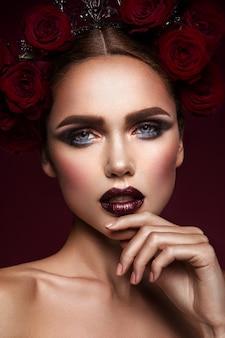 Belleza modelo de moda chica con maquillaje oscuro y rosas en el pelo
