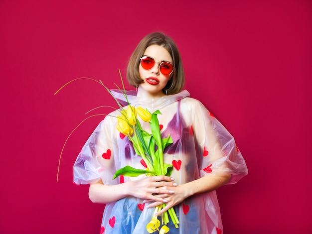 Belleza modelo mujer en impermeable con manojo de flores de primavera. muchacha hermosa con un ramo de flores amarillas del tulipán. mujer modelo sorprendida feliz que huele las flores. regalo del día de la madre. día de san valentín.