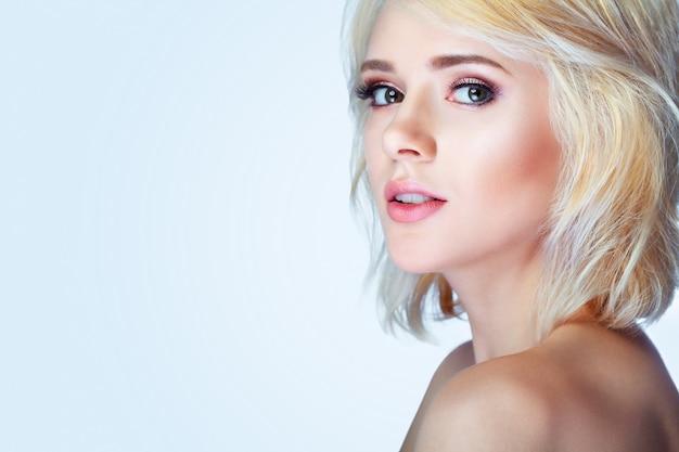 Belleza modelo sonriente con maquillaje natural y pestañas largas.
