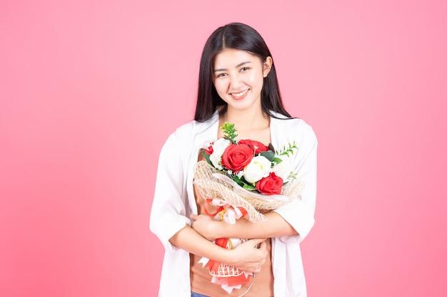Belleza de la mujer asiática linda chica sensación feliz celebración flor rosa roja y rosa blanca sobre fondo rosa
