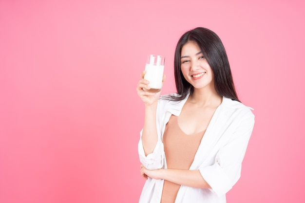 Belleza de la mujer asiática linda niña siente feliz bebiendo leche para una buena salud en la mañana sobre fondo rosa