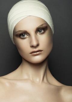 Belleza mujer vendaje cirugía plástica maquillaje cara en pared gris