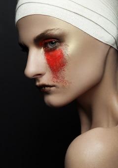 Belleza mujer vendaje cirugía plástica polvo rojo maquillaje en pared negra