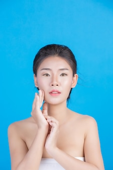 La belleza de las mujeres con imágenes perfectas de salud de la piel al tocar su rostro y sonreír como un spa para mimar su piel azul