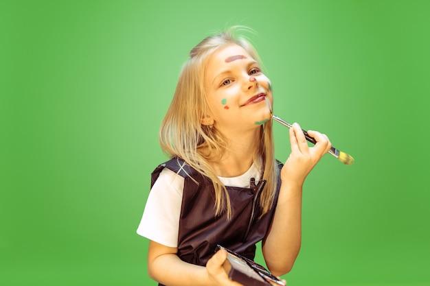 Belleza. niña soñando con la profesión de maquillador. concepto de infancia, planificación, educación y sueño. quiere convertirse en un empleado exitoso en la industria de la moda y el estilo, artista de peinado.