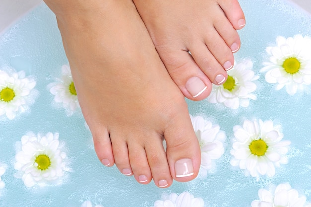Belleza y piernas femeninas limpias bajo el recipiente de agua