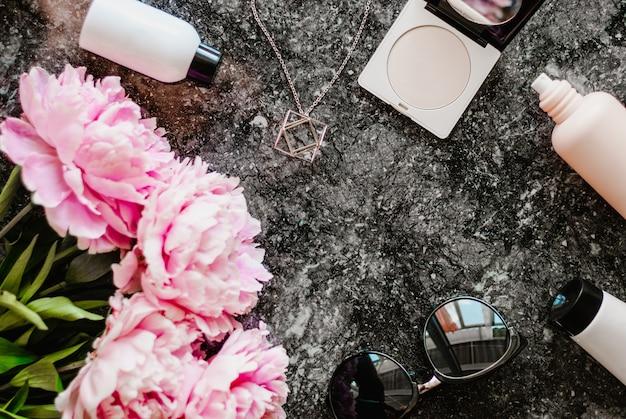 La belleza está plana con accesorios, perfumes, cosméticos y peonías sobre un fondo de mármol oscuro