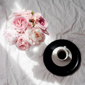 Belleza plana con café y ramo de flores rosas y piones.