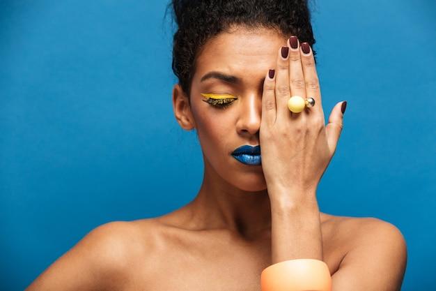 Belleza relajada mujer de raza mixta con cosméticos coloridos en la cara posando en la cámara cubriendo un ojo con la mano, aislado sobre la pared azul