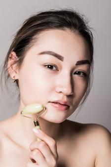 Belleza rosa jade piedra cara rodillo para terapia de masaje facial aislado en la pared gris. retrato de mujer asiática.