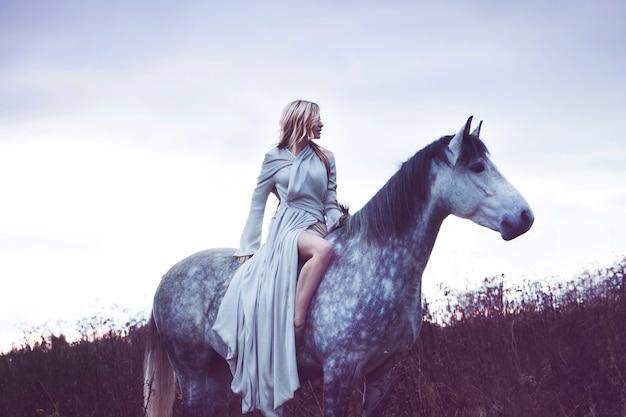 Belleza rubia con caballo en el campo, efecto de tonificación