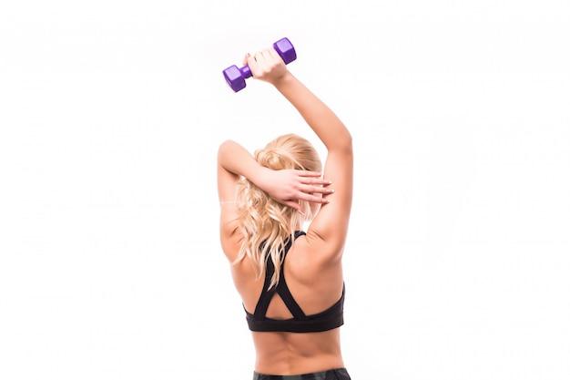 La belleza en top negro hace ejercicios para la espalda con elegantes mancuernas