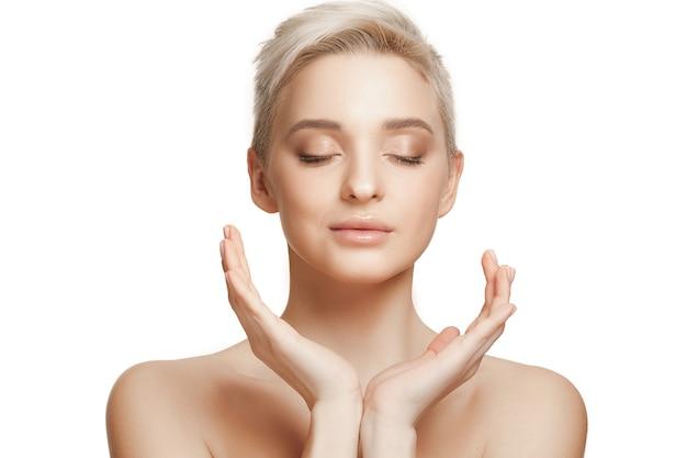 El bello rostro femenino. la piel de la cara perfecta y limpia en la pared blanca.