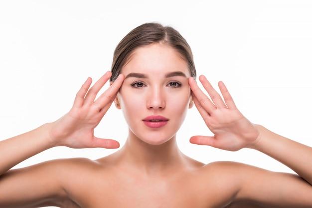 Bello rostro de mujer joven con la piel limpia y fresca aislada en la pared blanca