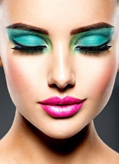 Bello rostro de una mujer con maquillaje verde vivo de ojos