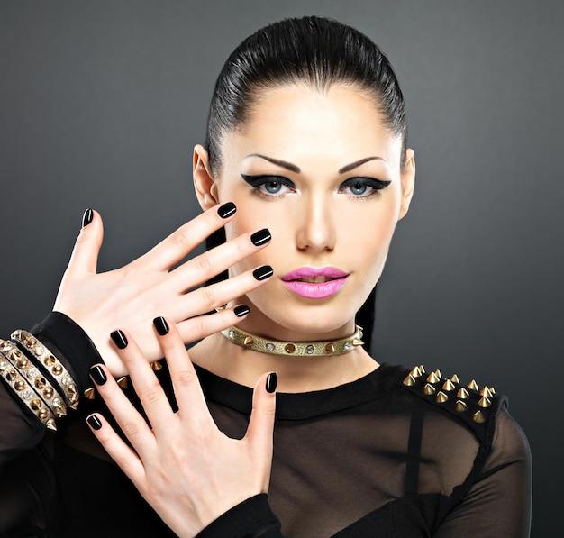 Bello rostro de mujer de moda con uñas negras y maquillaje brillante. chica sexy con estilo con espinas pulsera en el cuello