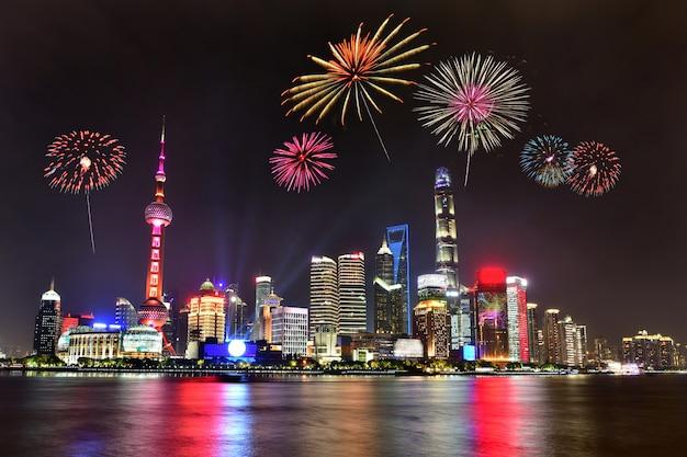 Bellos fuegos artificiales en el paisaje urbano de shanghai con las luces de la ciudad en el río huangpu