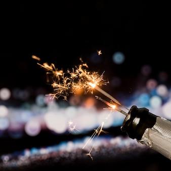 Bengala de fuego en botella de champagne sobre fondo bokeh por la noche