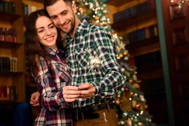Bengalas y un beso para navidad! joven hermosa besador y quema de bengalas. pareja amorosa en navidad decorado habitación.