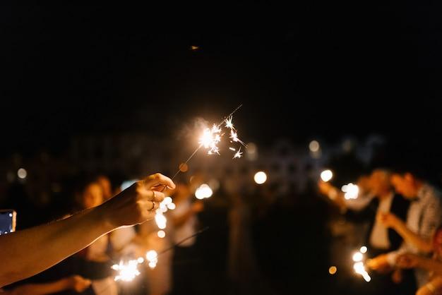 Bengalas en las manos en la noche de cerca