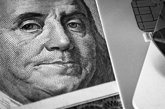 Benjamin franklin se enfrenta a un billete de cien dólares junto a una tarjeta de crédito