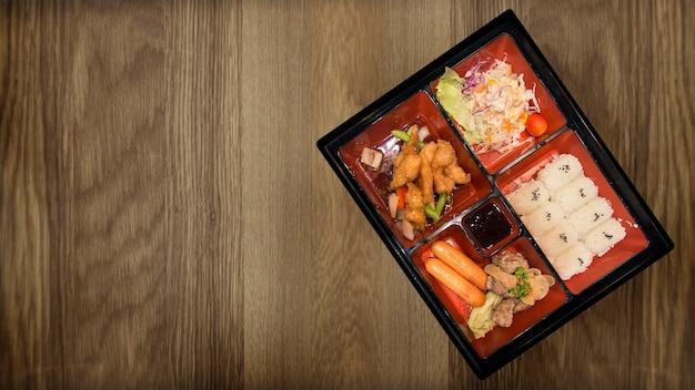 Bento conjunto de cerdo pollo y salsas tempura comida japonesa en restaurante de mesa de madera.