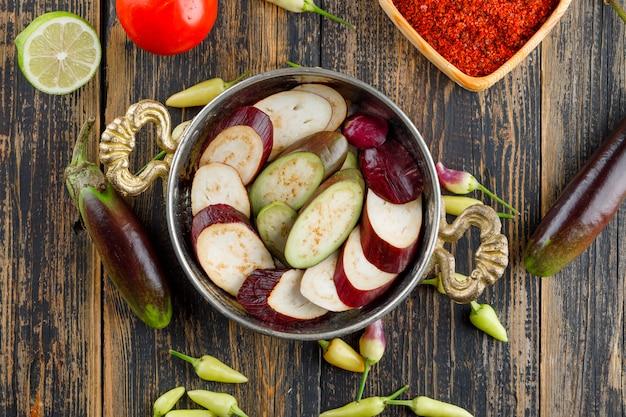 Berenjenas con especias, pimientos, tomate, lima en una sartén sobre madera, aplanada.
