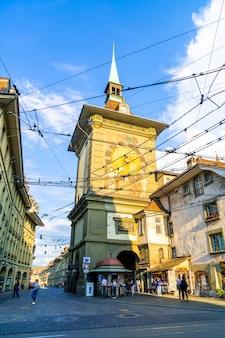 Berna, suiza - 23 de agosto de 2018: personas en el callejón de compras con la torre del reloj astronómico zytglogge de berna en suiza