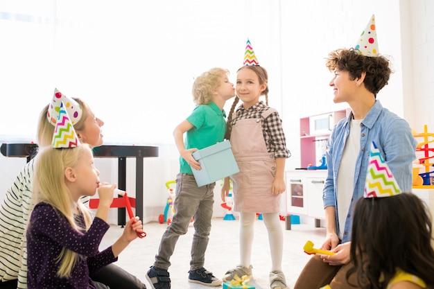 Besar a niña para regalo en la fiesta de cumpleaños de los niños