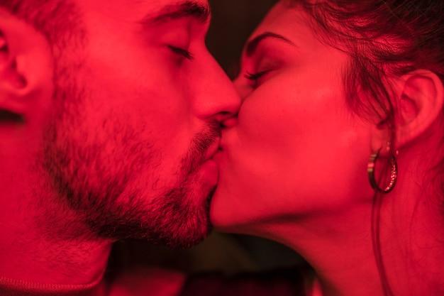 Beso de chico joven y dama atractiva enrojecimiento.