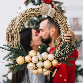 Beso hombre y mujer con corona de navidad.