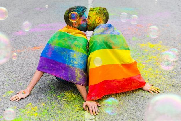 Beso lindos novios gay sentados en forma pavimentada