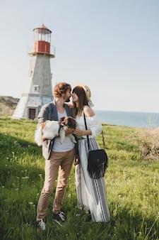 Besos elegante pareja hipster enamorada caminando con perro en campo, moda boho de estilo veraniego, romántico