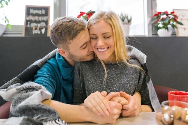 Besos joven pareja sentada en la cafetería juntos bajo una manta
