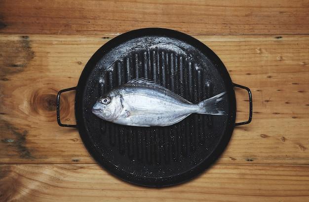 Besugo salvaje fresco en sartén listo para cocinar