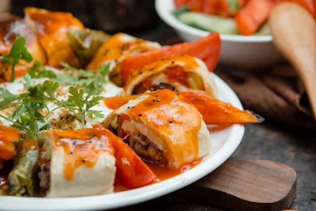 Beyti kebab envuelve en salsa de tomate con pimientos a la parrilla, de cerca