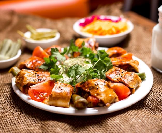 Beyti kebab servido con ayran y pepinillos