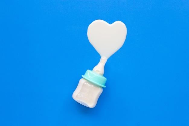 Biberón de leche para bebé sobre azul.