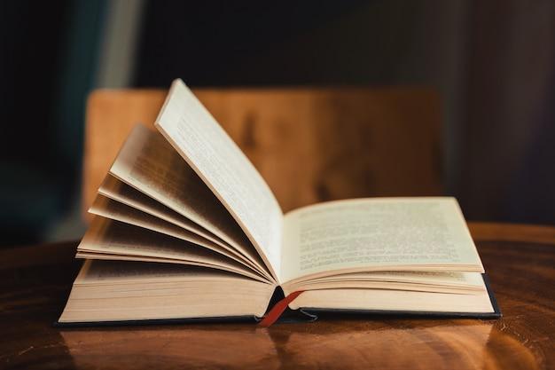 Biblia abierta para la devoción de la mañana en la mesa de madera con luz de ventana