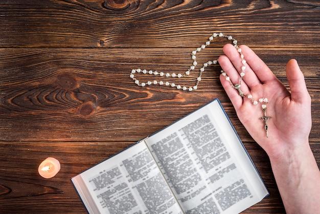 Biblia abierta, vela, cruz cristiana y manos humanas en madera