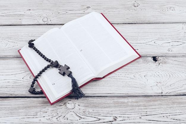 Biblia y el crucifijo en una mesa de madera blanca.