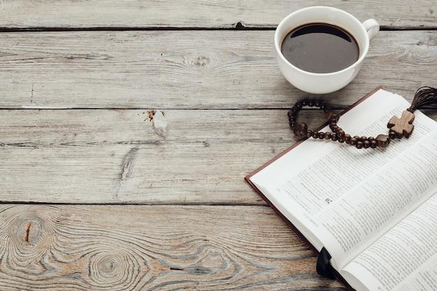 Biblia y un crucifijo en una vieja mesa de madera con taza de café