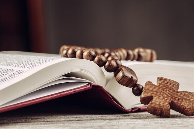 Biblia y un crucifijo en una vieja mesa de madera.