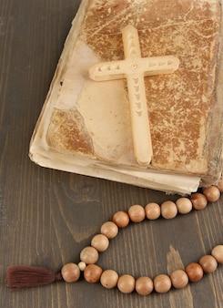 Biblia, rosario y cruz en primer plano de la mesa de madera