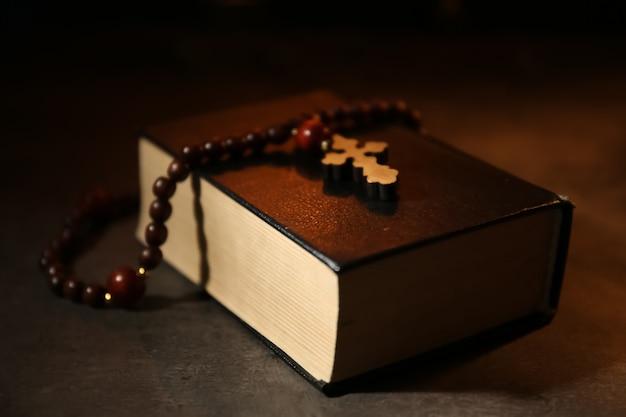 Biblia con rosario en mesa oscura